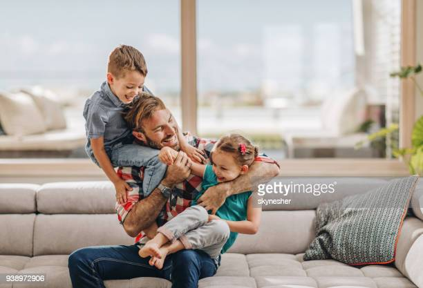 happy father playing with his small kids in the living room. - penthouse girls stock pictures, royalty-free photos & images