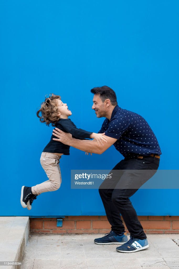 Happy father playing with son at blue wall : Stock Photo