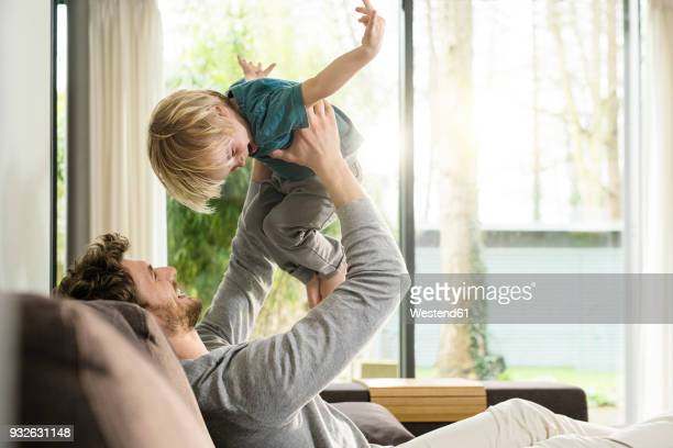 happy father playing with son on sofa at home - at home imagens e fotografias de stock