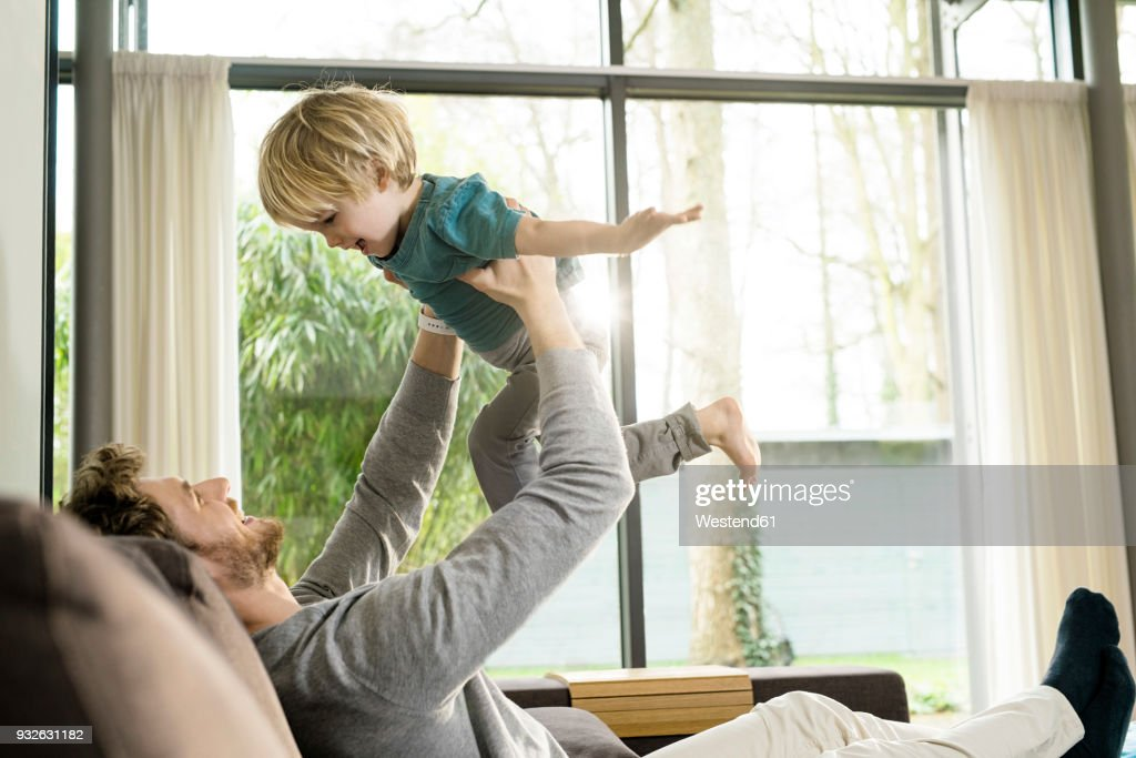 Happy father playing with son on sofa at home : Stock-Foto