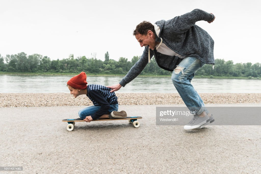 Happy father pushing son on skateboard at the riverside : Stock-Foto