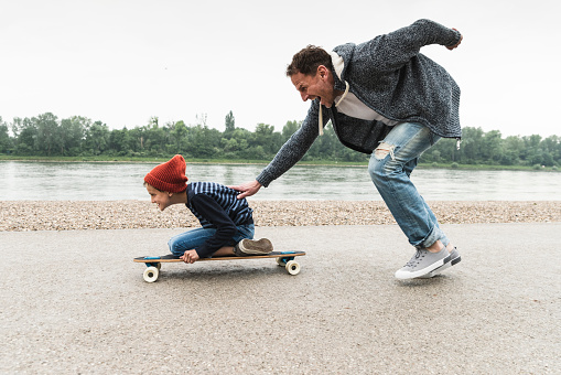 Happy father pushing son on skateboard at the riverside - gettyimageskorea