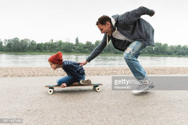 happy father pushing son on skateboard at the riverside - sostegno morale foto e immagini stock
