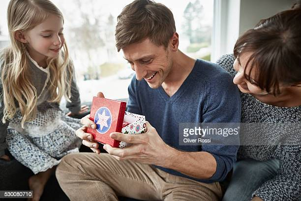 Happy father receiving gift from his family