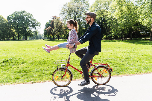 Happy father riding bicycle with daughter sitting on handlebar in a park - gettyimageskorea