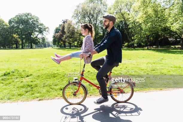 happy father riding bicycle with daughter sitting on handlebar in a park - family with one child stock pictures, royalty-free photos & images