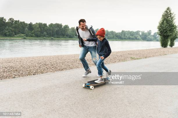 happy father running next to son on skateboard at the riverside - vater stock-fotos und bilder