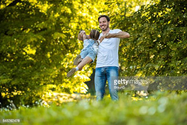 Happy father spinning his small girl in the park.