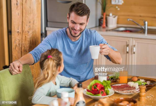 Happy father talking to his small daughter during breakfast at dining table.