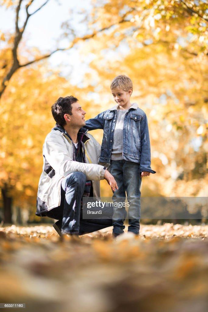 Gelukkig vader in gesprek met zijn zoon in het park. : Stockfoto