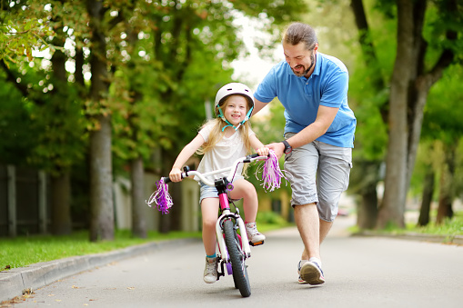 Happy father teaching his little daughter to ride a bicycle. Child learning to ride a bike. 938635616
