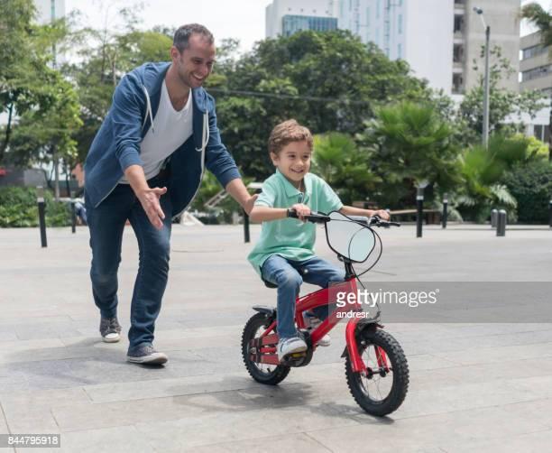 Enseñar A Los Chicos A Andar En Bici: Papas Latinos Enseñando Andar En Bici Fotografías E