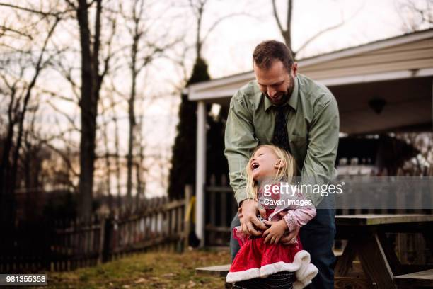happy father tickling daughter while standing at yard - tickling stock pictures, royalty-free photos & images