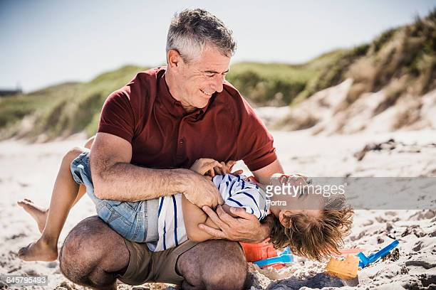 Happy father tickling son at beach