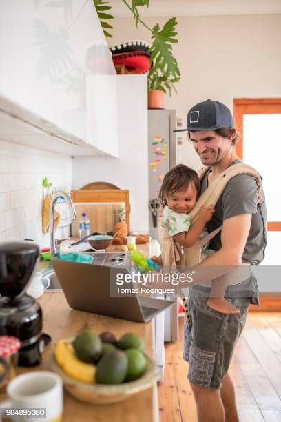 Happy father with a toddler in a baby carrier and a laptop in the kitchen