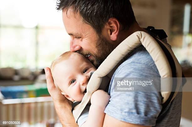 happy father with baby in baby carrier at home - padre amo de casa fotografías e imágenes de stock