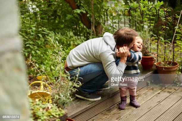 Happy father with little daughter on terrace