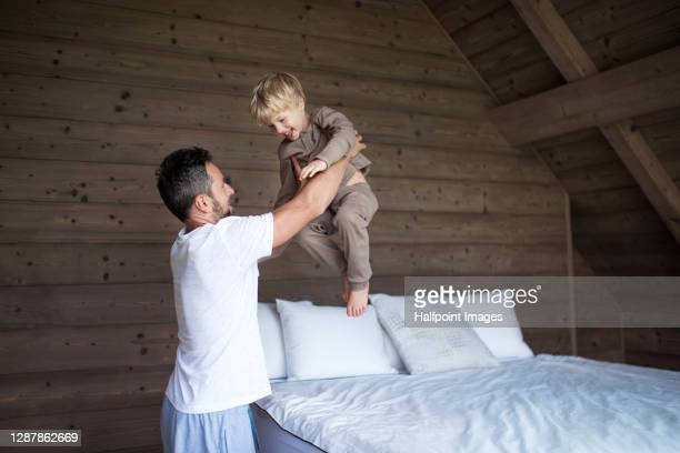 happy father with small son playing on bed on holiday. - pyjamas stock pictures, royalty-free photos & images
