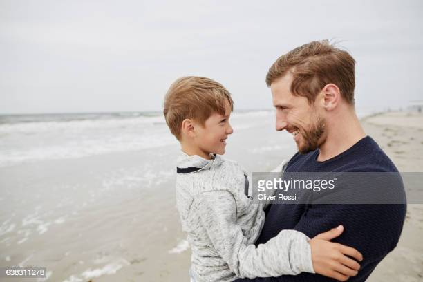 happy father with son on the beach - leanintogether stock pictures, royalty-free photos & images