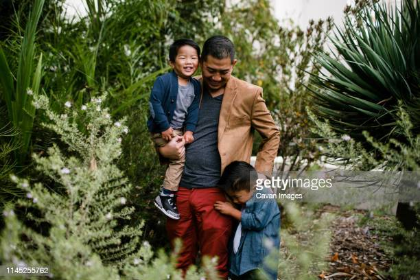 happy father with sons standing amidst plants in balboa park - balboa park stock photos and pictures