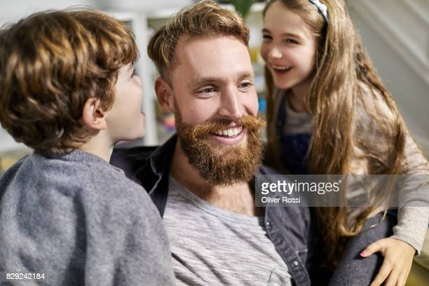 Happy father with two children at home