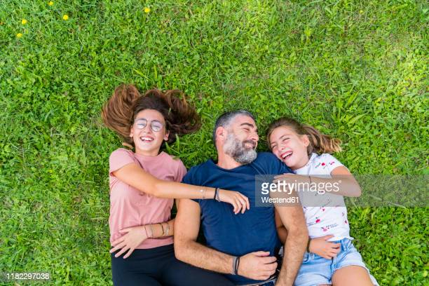 happy father with two daughters lying on a meadow - gras stock pictures, royalty-free photos & images