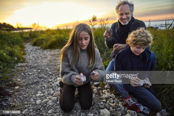 happy father with two kids collecting stones at the coast - rock stock pictures, royalty-free photos & images