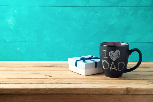 Happy Father's day concept with coffee mug and gift box over wooden background 1150096149