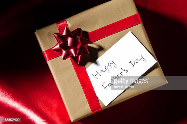 Happy Father's Day, gift with red ribbon against red background