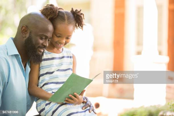 Happy Father's Day. Girl gives card to dad.