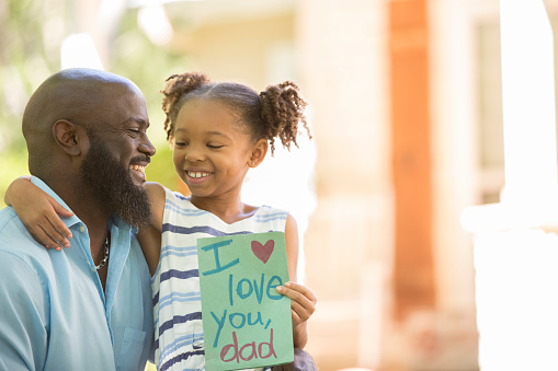 Happy Father's Day. Girl gives card to dad. 947482070