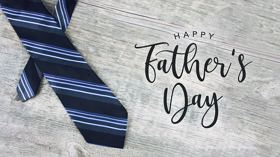 Happy Father's Day Text with Striped Tie Over Wood Background 961088734