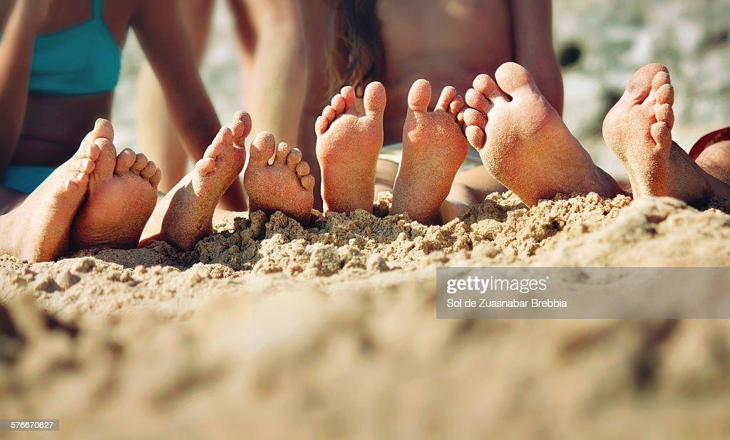 Happy feet. Barefoot family on the sand : Stock Photo