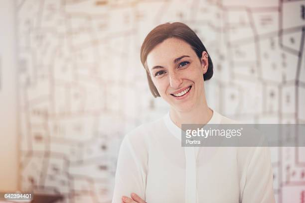 Happy female architect standing in office
