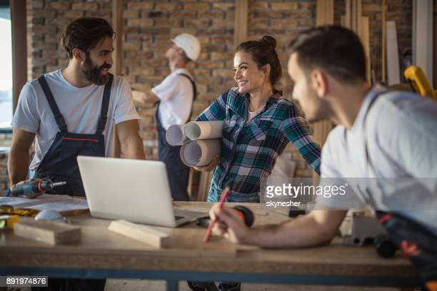 happy female architect talking to construction workers during home renovation process. - building contractor stock pictures, royalty-free photos & images