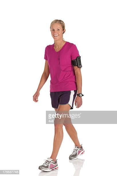 Happy female athlete walking