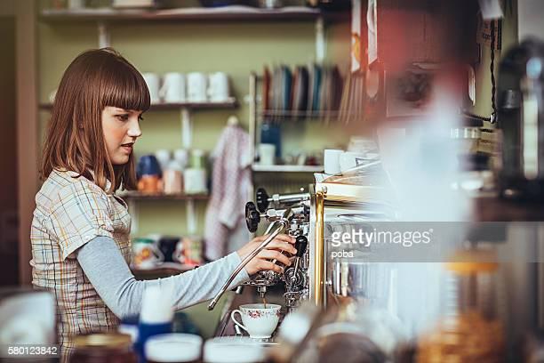 happy female barista  in retro  coffee shop