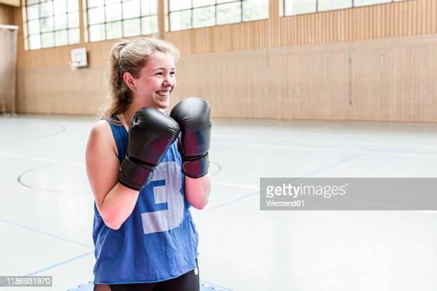 happy female boxer in sports hall - deporte de combate fotografías e imágenes de stock
