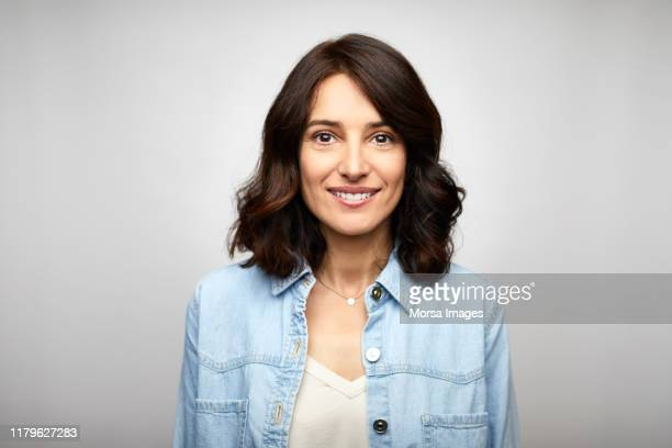 happy female brunette ceo wearing blue denim shirt - glimlachen stockfoto's en -beelden