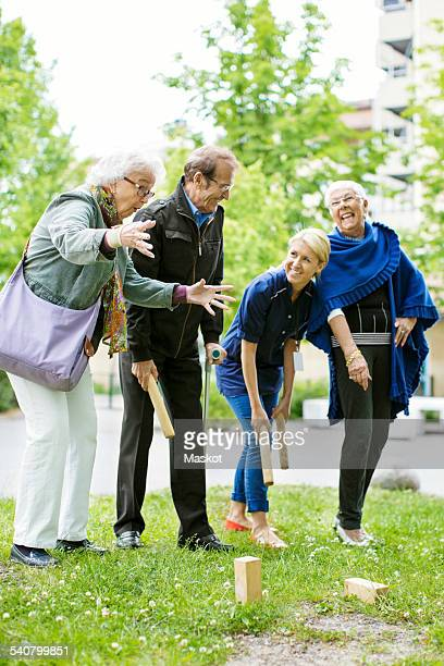 Happy female caretaker playing kubb game with senior people at park