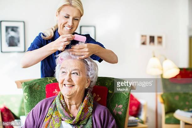 Happy female caretaker putting curlers to senior womans hair at nursing home