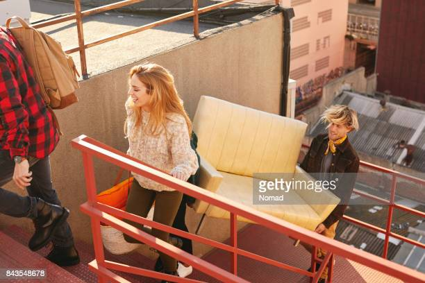 happy female climbing steps with males on building. high angle view of multi-ethnic friends are carrying sofa while moving towards terrace. they are wearing casuals. - carrying imagens e fotografias de stock