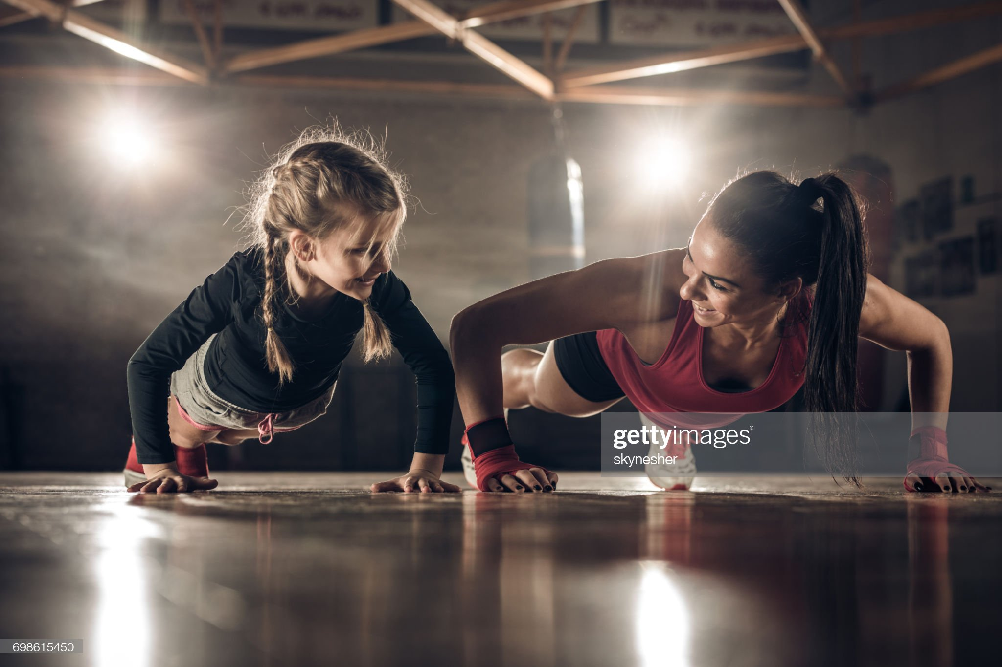 Happy female coach and little girl doing push-ups in a health club. : Stock Photo