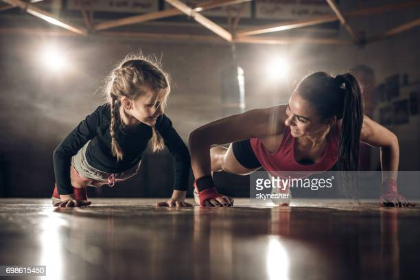 Happy female coach and little girl doing push-ups in a health club.