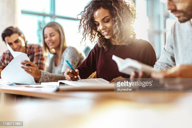 happy female college student reading a book on a class. - college student stock pictures, royalty-free photos & images