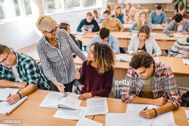 happy female college student talking to senior professor on a class in the classroom. - college student stock pictures, royalty-free photos & images