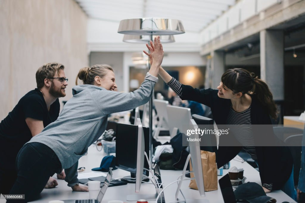 Happy female computer programmers giving high-five over desk in office : Stock Photo