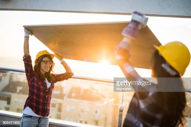 Glücklich weibliche Bauarbeiter tragen Holzbohle auf der Terrasse bei Sonnenuntergang.