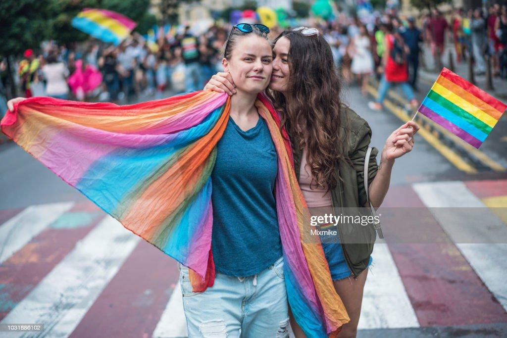 幸せな女性のカップルのハグ、ゲイプライド パレードでキス : ストックフォト