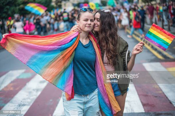 happy female couple hugging and kissing at the gay pride parade - lesbica bacio foto e immagini stock